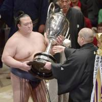 Kisenosato receives the trophy on Sunday after winning the New Year Grand Sumo Tournament. | KYODO