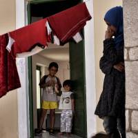 Children standing at the entrance of their apartment in a summer resort on April 20, 2016, in Myrsini, Greece, which shelters nearly 350 Syrian refugees. According to the Japanese ministry, only 69 Syrian citizens sought refugee status in Japan from 2011 through 2016.   AFP-JIJI