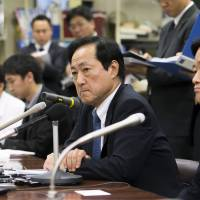 Yasuhiro Sato (center), president and chief executive officer of Mizuho Financial Group Inc., listens during a news conference in Tokyo on Nov. 14.   BLOOMBERG