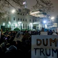Protesters hold up signs against U.S. President Donald Trump in front of the U.S. Consulate General in the port city of Hamburg, northern Germany, on Tuesday. | AFP-JIJI