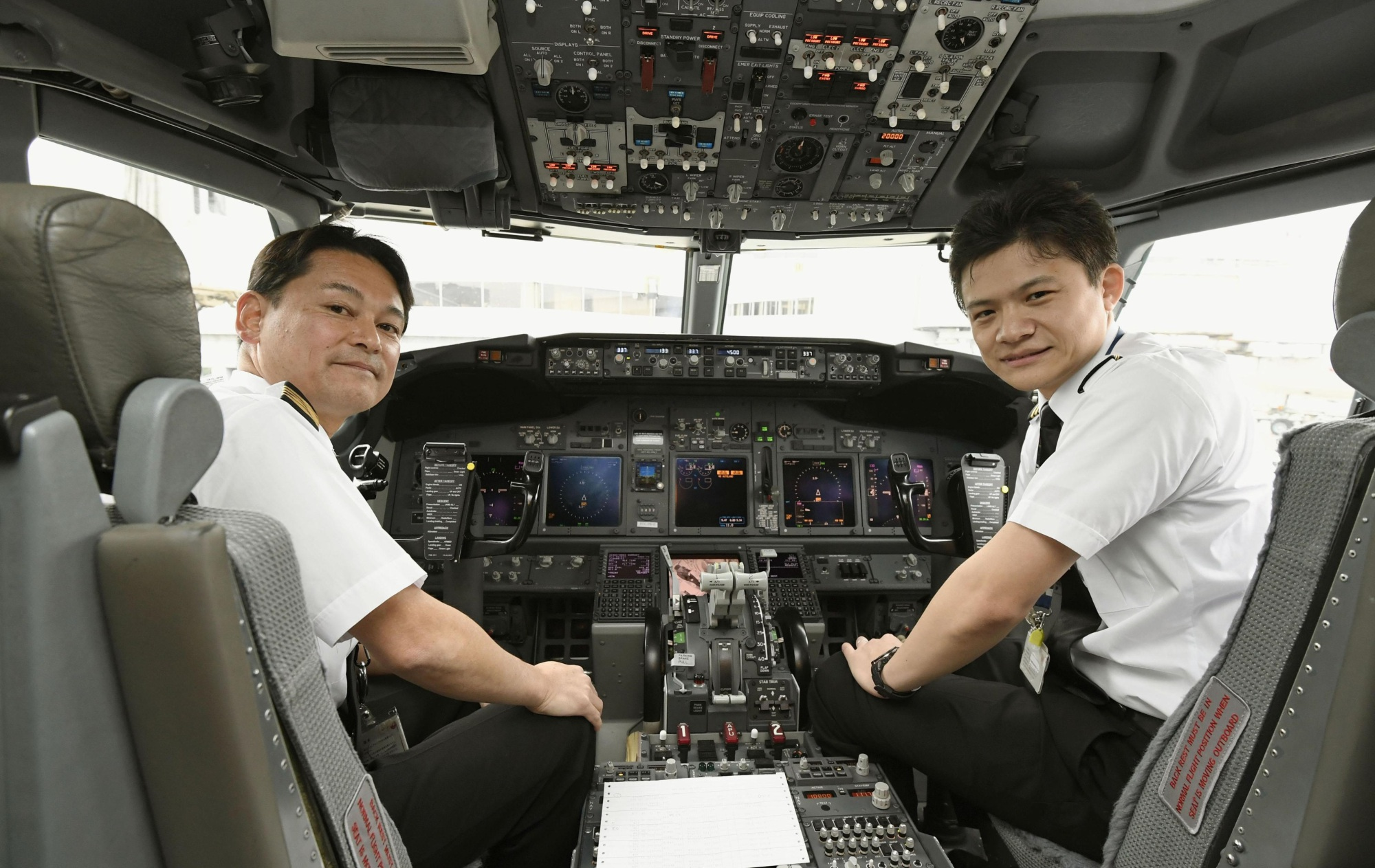 Tatsuhiko Senzaki (right) gets ready for his first JAL flight as a copilot at Tokyo's Haneda airport on Monday. | KYODO
