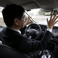 Nissan's head of automated driving, Tetsuya Lijima, sits at the controls of a modified Nissan Leaf driverless car during its first demonstration on public roads in Europe, in London Monday. | REUTERS