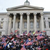 Muslims, members of the Yemeni community and others wave American and Yemeni flags as they gather on the steps of Brooklyn's Borough Hall to protest President Donald Trump's temporary travel ban on citizens from seven predominantly Muslim countries, Thursday in New York. | AP