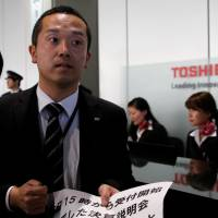 A Toshiba Corp. spokesman briefs the media on the firm's decision to ask for a delay in releasing its earnings figures at the company's Tokyo headquarters on Tuesday. | REUTERS