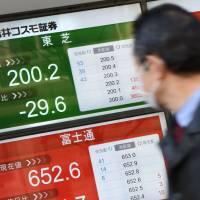A man looks at a screen displaying Toshiba's share price in front of a securities company in Tokyo on Wednesday. | AFP-JIJI