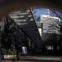A man is seen walking toward Toshiba Corp.'s headquarters in Tokyo last month. The firm is seeking to make up for a huge write-down in its U.S. nuclear unit. | BLOOMBERG