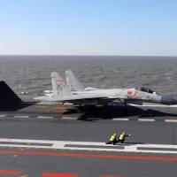 This file photo taken on Dec. 14 shows a Chinese J-15 fighter jet preparing to take off from the deck of the Liaoning aircraft carrier during military drills in the Bohai Sea, off China's northeast coast. China continues to arm itself faster than other countries to the point of moving towards near parity with the West in some military areas, according to the annual report of the International Institute for Strategic Studies (IISS) released on Tuesday. | AFP-JIJI