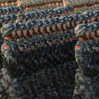 Chinese soldiers conduct a practice at dawn ahead of a military parade later in the morning at Tiananmen Square in Beijing on Sept. 3, 2015, to mark the 70th anniversary of victory over Japan and the end of World War II. China continues to arm itself faster than other countries to the point of moving toward near parity with the West in some military areas, according to the annual report of the International Institute for Strategic Studies (IISS) released Tuesday. | AFP-JIJI