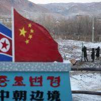 Chinese paramilitary policemen are seen building a fence near a marker depicting the North Korean and Chinese national flags with the words 'China North Korea Border' at the border town of Tumen in China's Jilin province in December 2012. | AP