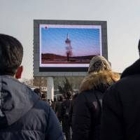 People in Pyongyang watch a public broadcast on Feb. 13 about the launch of a surface-to-surface medium long-range Pukguksong-2 ballistic missile last week. | AFP-JIJI