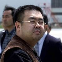 Kim Jong Nam exits a police van to board a plane to Beijing at Narita airport after being caught using a false passport while trying to go to Tokyo Disneyland in 2001.   AP
