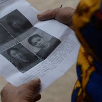 Nguyen Thi Vy, 54, mother-in-law of Doan Thi Huong, a suspect involved in the assassination of Kim Jong Nam, looks at handouts and published photographs of the four arrested suspects including Huong at Huong's family home in Vietnam. | AFP-JIJI
