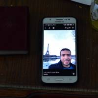 A picture taken on Sunday shows a picture of Abdallah El-Hamahmy, an Egyptian suspected of being the machete attacker in Paris's Louvre museum, displayed on a phone at the family home in the Nile delta city of Mansura, some 120 km north of Cairo. Abdallah's father said his son showed no sign of radicalization and he believed in his innocence. | AFP-JIJI