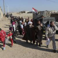 Displaced Iraqis flee their homes due to fighting between Iraqi security forces and Islamic State militants, in the Mamun neighborhood on the western side of Mosul, Iraq, Saturday. | AP