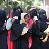 Rohingya women wait with vouchers to collect relief distributed by the Bangladesh Red Crescent Society at Kutupalang Unregistered Refugee Camp in Cox's Bazar, Bangladesh, Monday. | REUTERS
