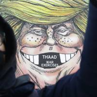 A South Korean protester stands in front of a cartoon depicting U.S. President Donald Trump during a rally against visiting U.S. Defense Secretary Jim Mattis outside the government complex in Seoul on Thursday. The U.S. plans to deploy the THAAD anti-missile system to defend the South and Japan against attacks by North Korea. | AP