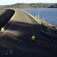 A worker stands in the middle of the road, to monitor a road closure, atop the Oroville Dam on Tuesday in Oroville, California. | AP
