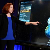 Space Telescope Science Institute astronomer Nikole Lewis uses a graphic to compare the size of Earth (bottom) with a recent discovery of an exoplanet, during a news conference to present new findings on exoplanets, planets that orbit stars other than Earth's sun, in Washington Wednesday. | REUTERS