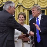 U.S. President Donald Trump shakes hands with Rex Tillerson as Tillerson's wife, Renda St. Clair, looks on after Tillerson was sworn in as secretary of state at the White House in Washington on Feb. 1. | AFP-JIJI
