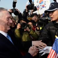 U.S. Defense Secretary James Mattis shakes hands with pro-U.S. activists during his visit to the national cemetery in Seoul, South Korea, on Friday. | REUTERS