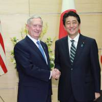 U.S. Defense Secretary James Mattis and Prime Minister Shinzo Abe shake hands at the Prime Minister's Office on Friday. | REUTERS