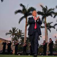 U.S. President Donald Trump arrives to a marching band at Trump International Golf Club in West Palm Beach, Florida, on Sunday. | REUTERS