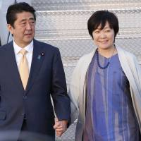Prime Minister Shinzo Abe and his wife, Akie, exit Air Force One after arriving in Florida with U.S. President Donald Trump on Feb. 10. | AP