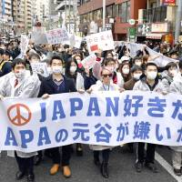Protesters march on a street in Tokyo's Shinjuku Ward on Sunday to protest Nanking Massacre denier Toshio Motoya, president of the Apa Hotel chain. The banner reads: 'We love Japan. We hate Motoya of Apa.' | KYODO