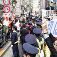 People protesting Apa Group President Toshio Motoya and those condemning the rally face off in Shinjuku Ward, Tokyo, on Feb. 5. | KYODO