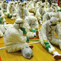 Saga Prefectural Government officials take a break from culling thousands of infected chickens Sunday at a gymnasium in the town of Kohoku. | KYODO