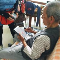 An elderly Japanese man enters his blood pressure and other information to send to a health care service in Chiang Mai, Thailand, in January. | GREEN LIFE SUPPORT CO. / VIA KYODO