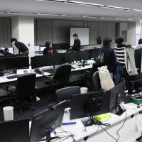 Employees at Nagoya-based ad venture Quartet Communications get ready to leave their office as 6 p.m. rolls around. | CHUNICHI SHIMBUN