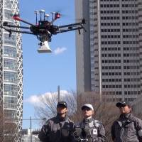 Officials in Shinjuku Central Park in Tokyo on Saturday test the effectiveness of using a drone to respond to a natural disaster. | KAZUHIRO KOBAYASHI