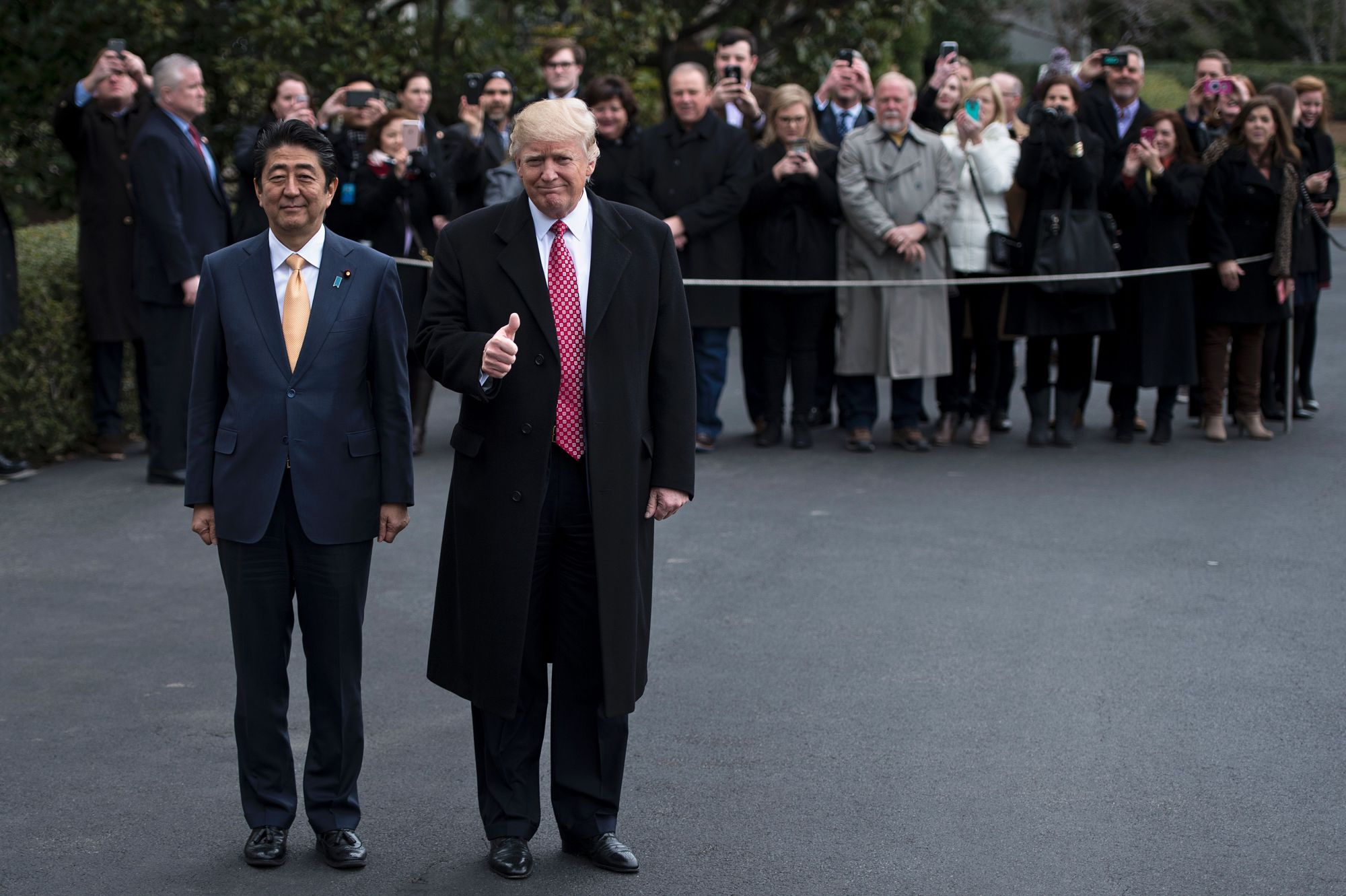 U.S. President Donald Trump gives a thumbs-up while walking to Marine One with Prime Minister Shinzo Abe on the South Lawn of the White House on Friday. | AFP-JIJI