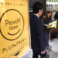 An official at the Daimaru department store in Tokyo hands out leaflets on the Premium Friday campaign on Feb. 17. | KYODO