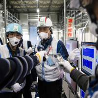 A Tokyo Electric employee leads a media tour Thursday at the crippled Fukushima No. 1 plant in Fukushima Prefecture.   AFP-JIJI
