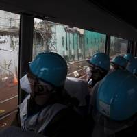 Journalists aboard a bus get a glimpse of the damaged No. 4 reactor building during a media tour Thursday at the Fukushima No. 1 plant.   AFP-JIJI