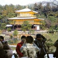 Tourists take photos of snow-dusted Kinkakuji Temple in Kyoto in December. The city is nurturing local tour guides who can provide in-depth knowledge on Kyoto in foreign languages. | KYODO