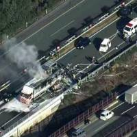 Burning vehicles are seen on the Kyushu Expressway in Kumamoto Prefecture after a pileup on Tuesday. | KYODO