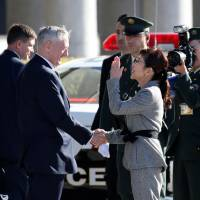 U.S. Defense Secretary Jim Mattis (center left) and Defense Minister Tomomi Inada shake hands before they review an honor guard at the Defense Ministry in Tokyo on Saturday. | REUTERS