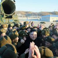 A photo published Monday by the Rodong Sinmun, a North Korean newspaper, shows North Korean leader Kim Jong Un celebrating the launch of a Pukguksong-2 missile. | KYODO
