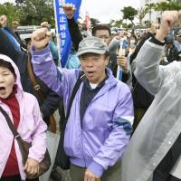 Plaintiffs and their supporters rally in front of the Naha branch of the Naha District Court on Thursday. | KYODO