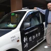 Katsuyoshi Arasaki stands besides a car from his designated driver service company in the city of Okinawa on Jan. 26. | THE OKINAWA TIMES