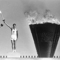Runner Yoshinori Sakai holds up the Olympic torch after lighting the cauldron during the opening ceremony for the 1964 Olympics in Tokyo. | KYODO