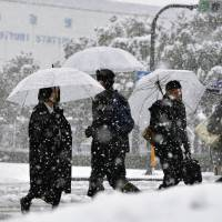 Heavy snowfall in front of Tottori Station on Friday. | KYODO