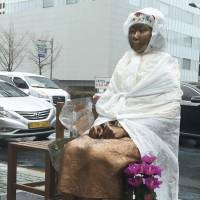 A 'comfort women' statue stands in front of the Japanese Consulate in Busan, South Korea, on Monday. | YONHAP/ VIA KYODO