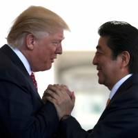 Prime Minister Shinzo Abe is greeted by U.S. President Donald Trump ahead of their joint news conference at the White House in Washington, D.C., on Friday. | REUTERS
