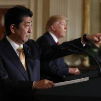 Prime Minister Shinzo Abe calls on a reporter as he participates in a joint new conference with President Donald Trump in the East Room of the White House, in Washington on Friday. | AP