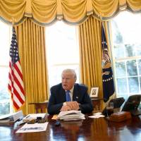 U.S. President Donald Trump gives an interview from his Oval Office desk in the White House on Thursday. | REUTERS