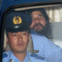 In this August 1995 file photo, Shoko Asahara, leader of the Aum Shinrikyo cult, is seen being driven away from the Tokyo District Court to the Metropolitan Police headquarters after an extension of his detention was approved. The doomsday cult that carried out a deadly nerve gas attack on Tokyo's subways the same year also used the VX nerve agent suspected in the killing of North Korean leader Kim Jong Un's half-brother. | AP
